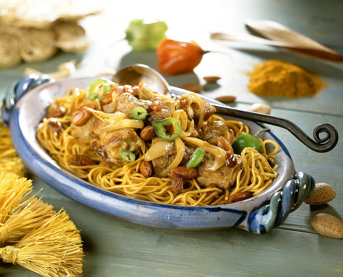 Beef with onions, almonds, raisins on curry noodles