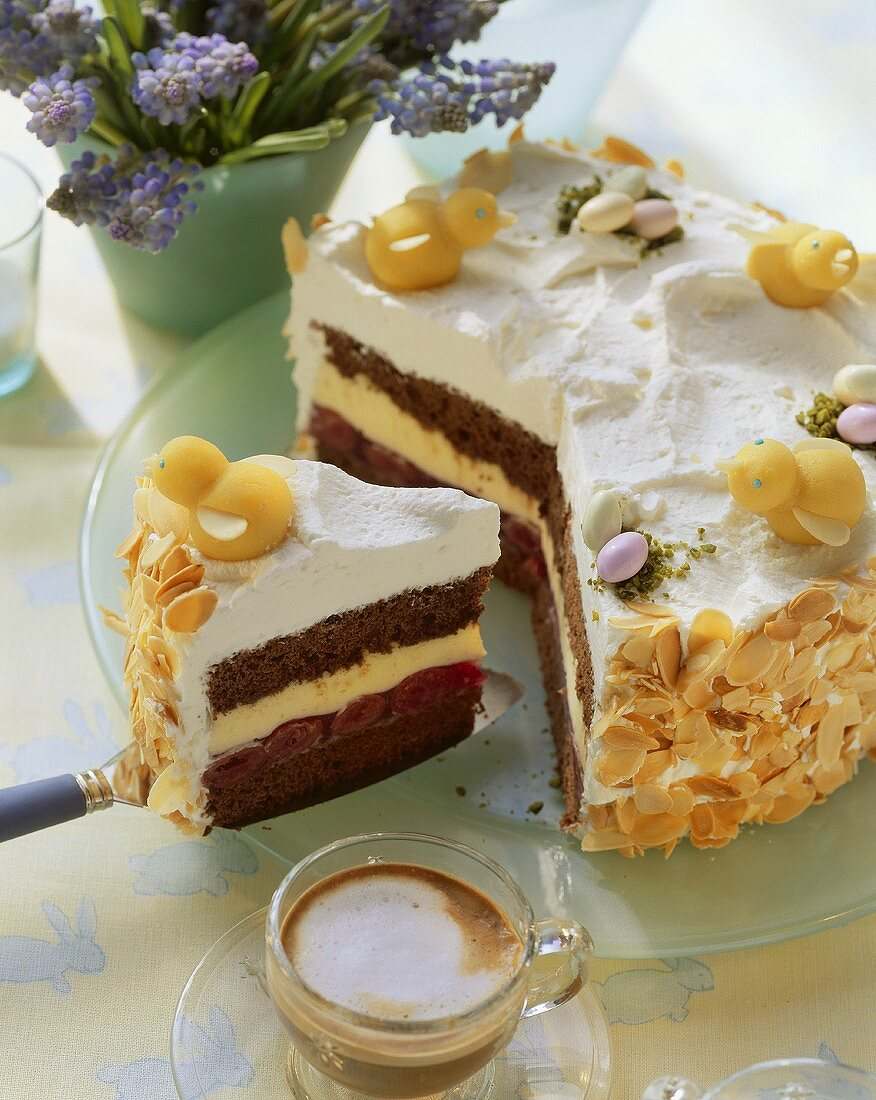 Easter cake with marzipan chicks, white coffee beside it