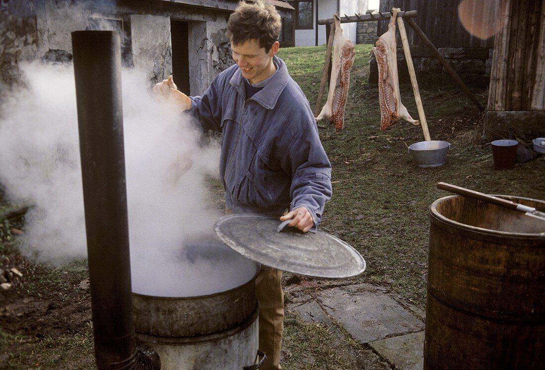 Butchering a pig: farmer at scalding pot