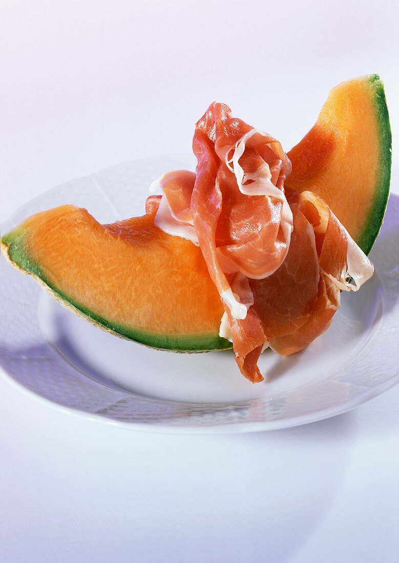 A piece of netted melon with raw ham on plate