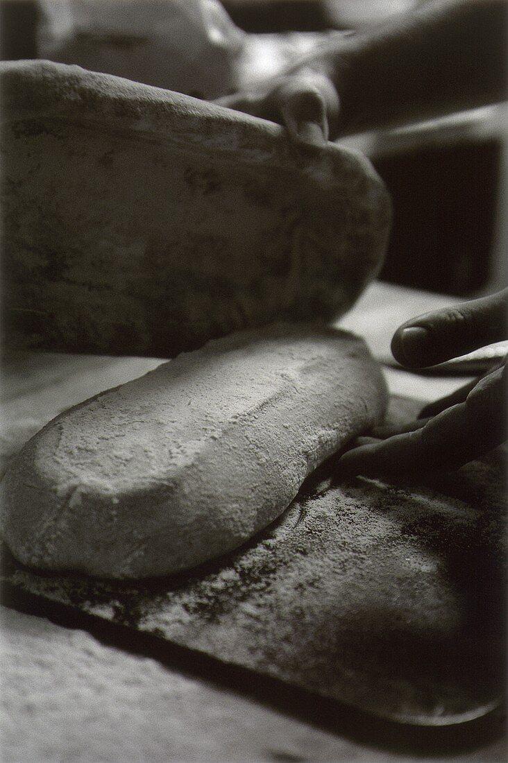 Bread dough being taken out of tin on to baking sheet (b/w)
