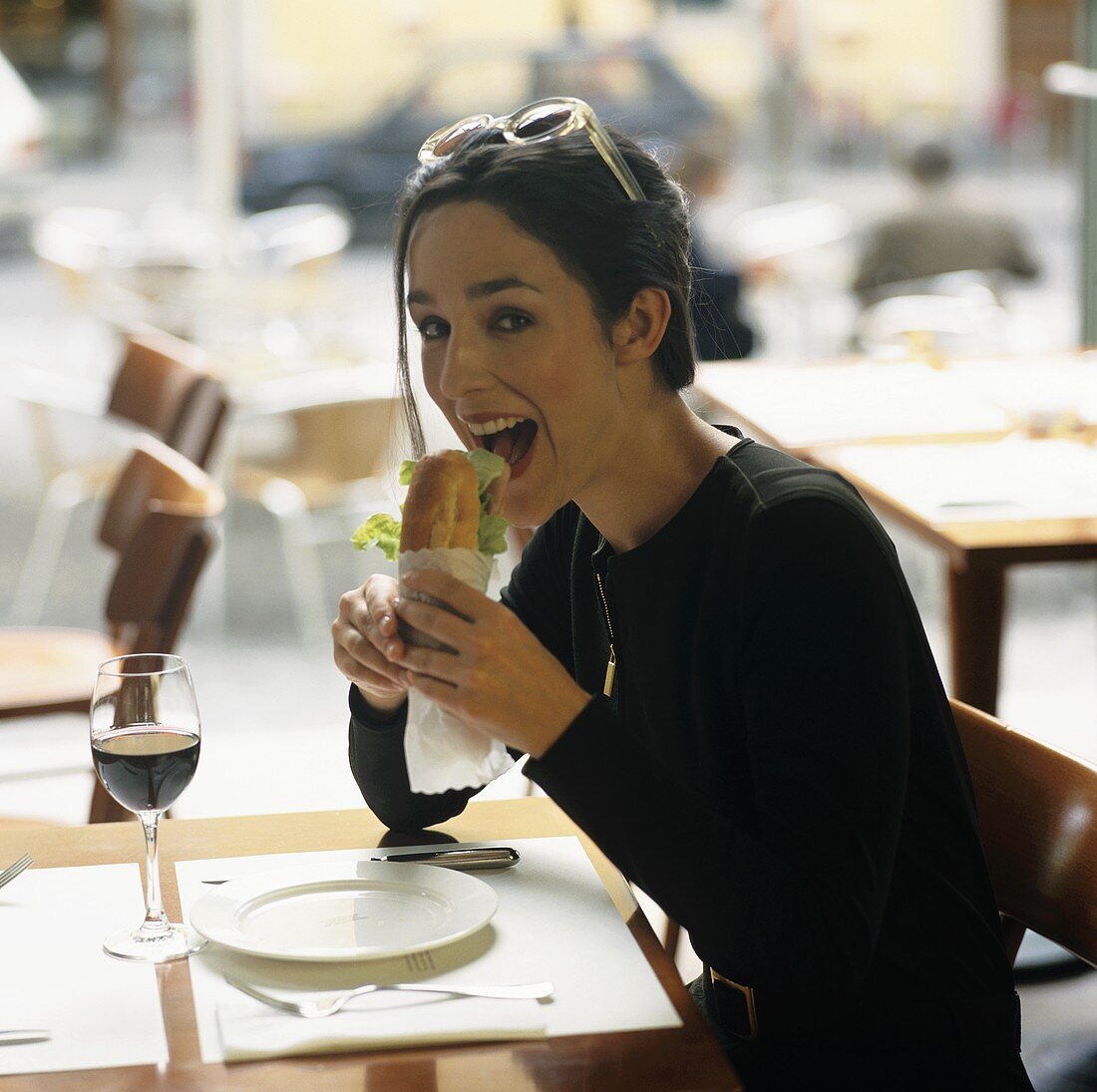 Young woman sitting in restaurant eating baguette sandwich