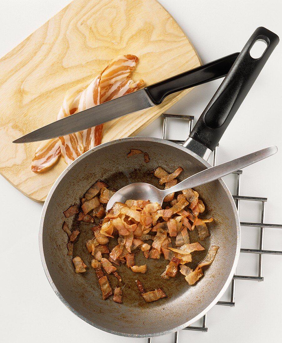 Frying rashers of bacon in a pan (until fat runs)