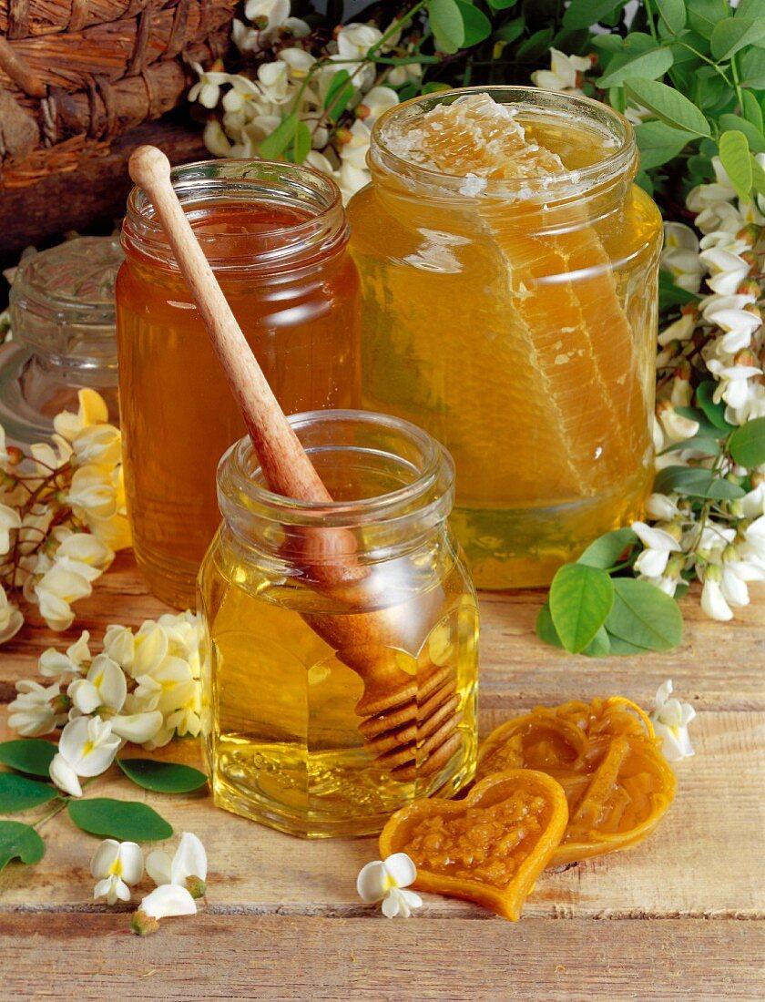 Three jars of honey with honey spoon and honeycomb
