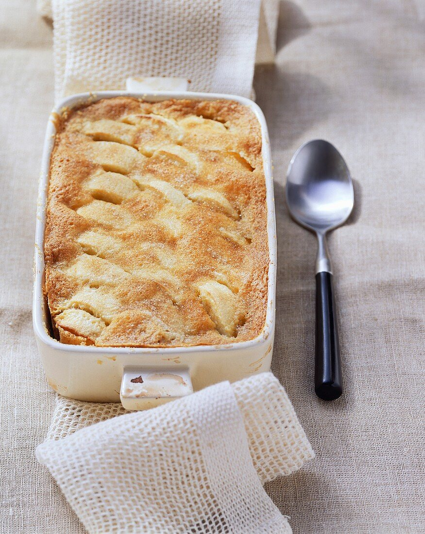 Sweet apple pudding with cinnamon in baking dish
