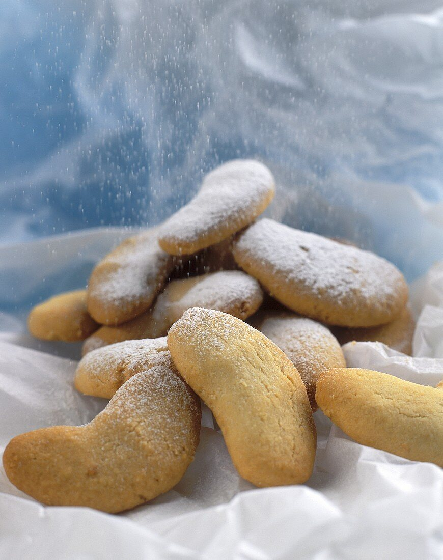 Almond crescents being dusted with icing sugar