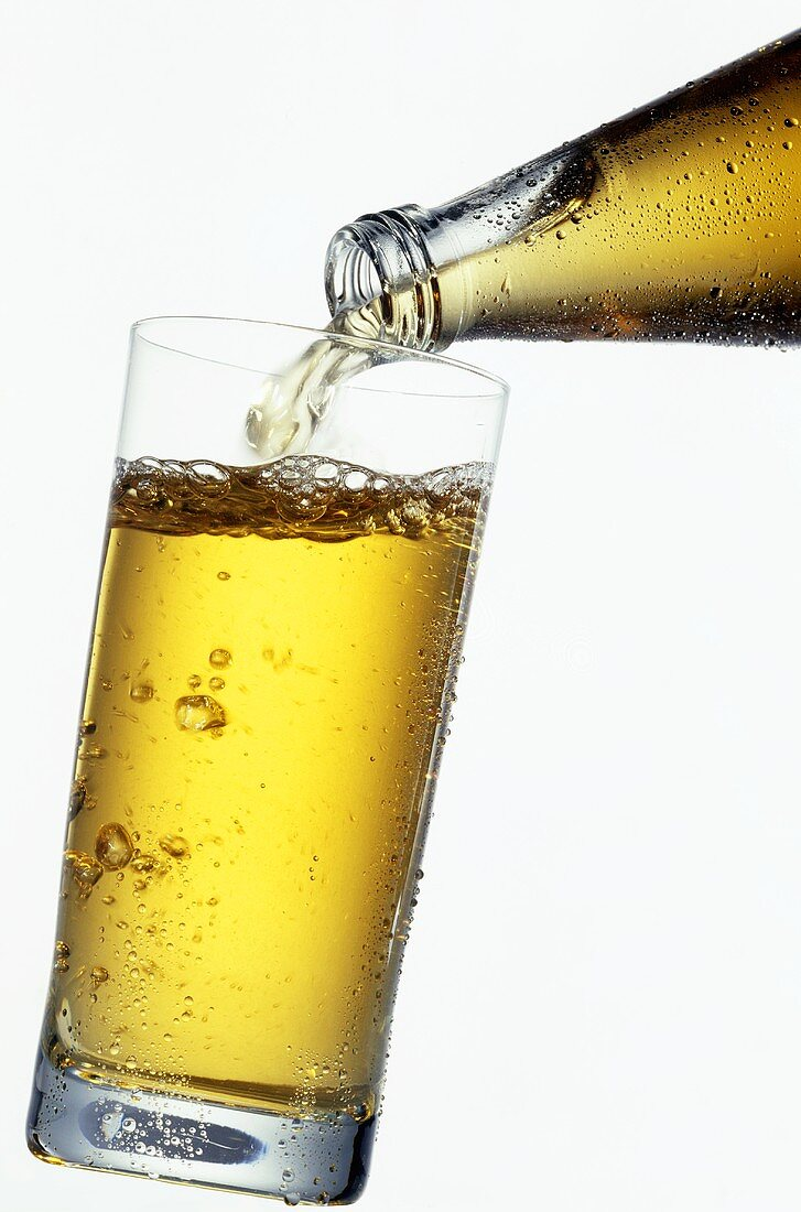 Pouring apple juice drink into a glass