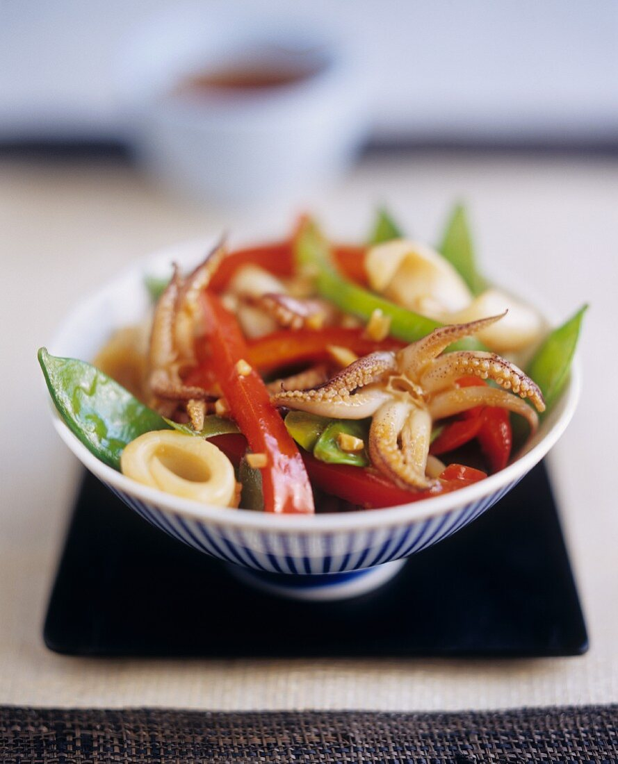 Chinese stir-fried cuttlefish with vegetables in bowl