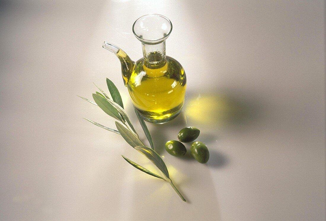 Olive oil in glass jug with olives and branch