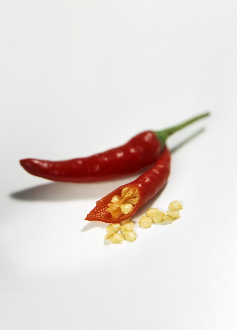 Two red chilis, one cut open with seeds