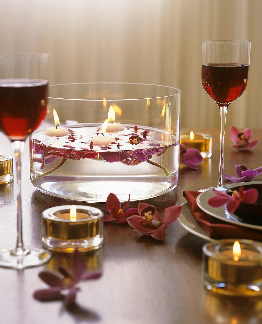 Bowl of flowers & candles on table laid for romantic meal