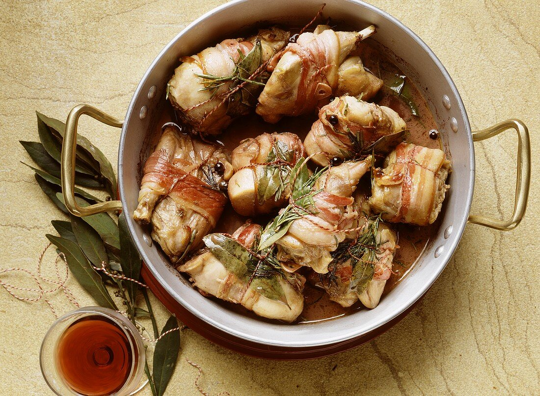Braised rabbit pieces wrapped in bacon and bay leaf