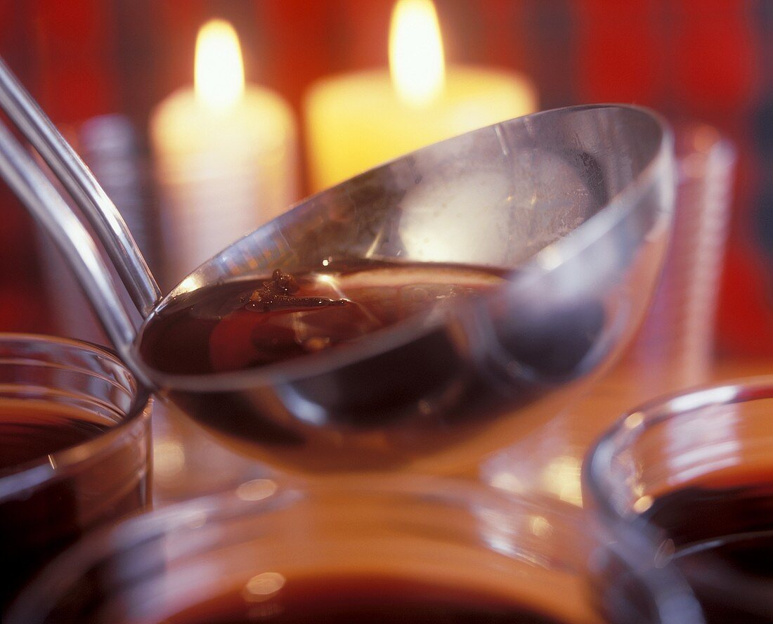 Wine punch in a ladle, with candles in background