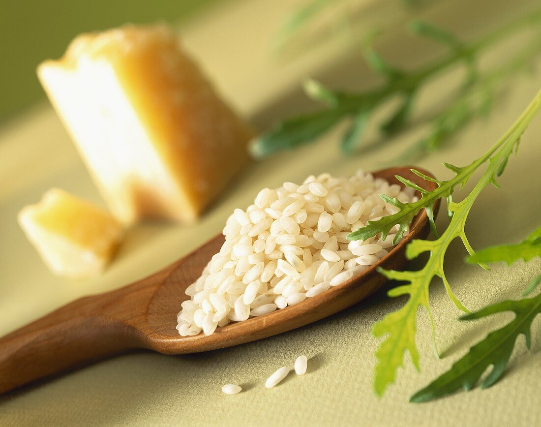 Risotto rice on a wooden spoon; rocket and piece of parmesan