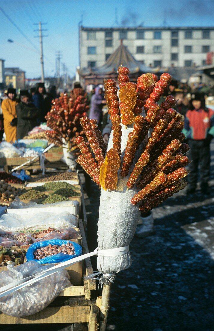 Tang Hulu: candied rose hips at a market (Northern China)
