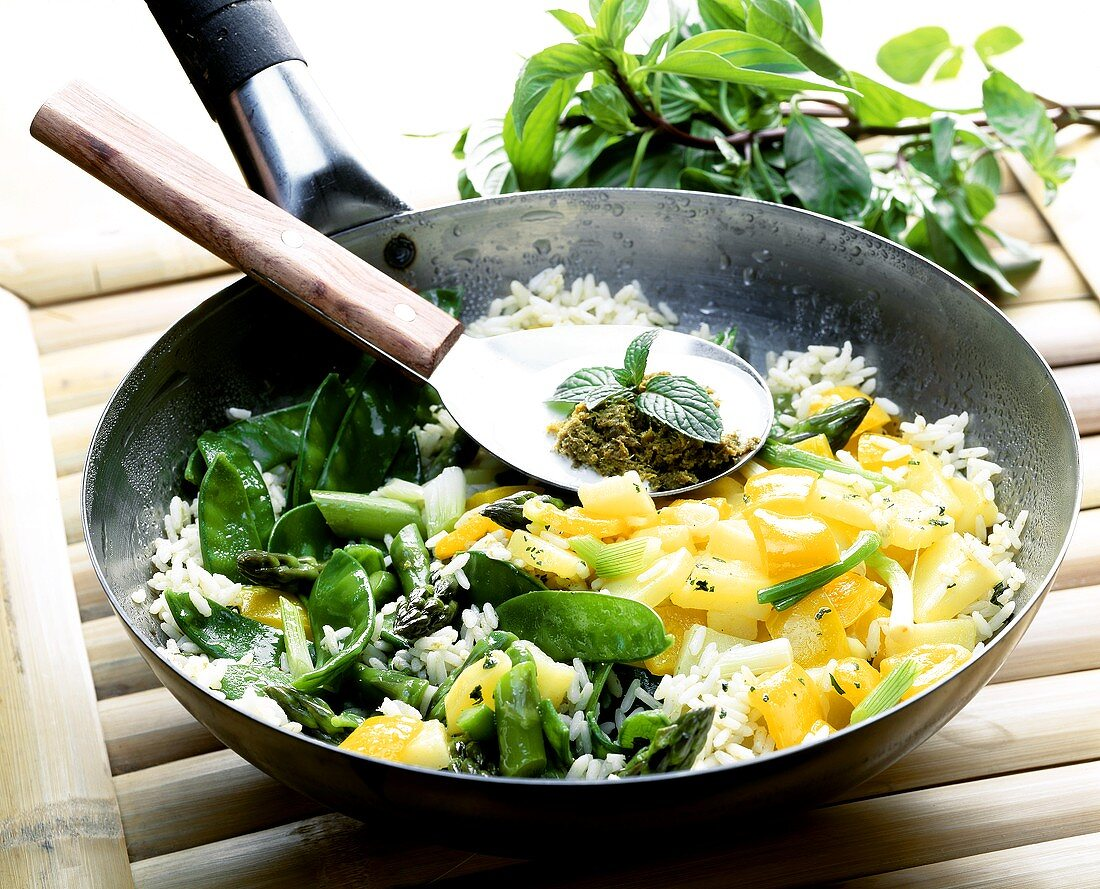 Rice & vegetable wok; spoon with Thai curry sauce ingredients