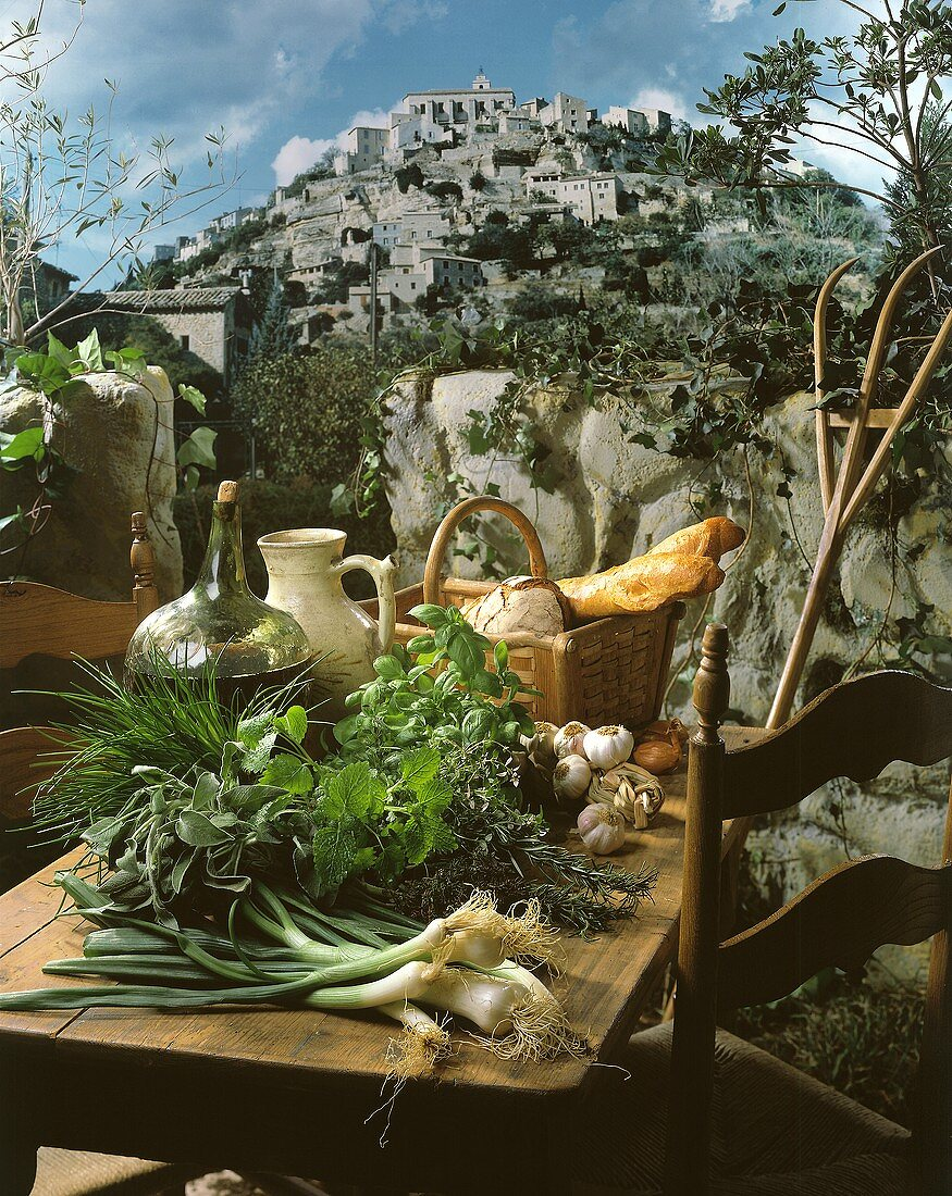 Herbs, onions, wine and bread on a rustic wooden table on a terrace with a view of a historic mountain village