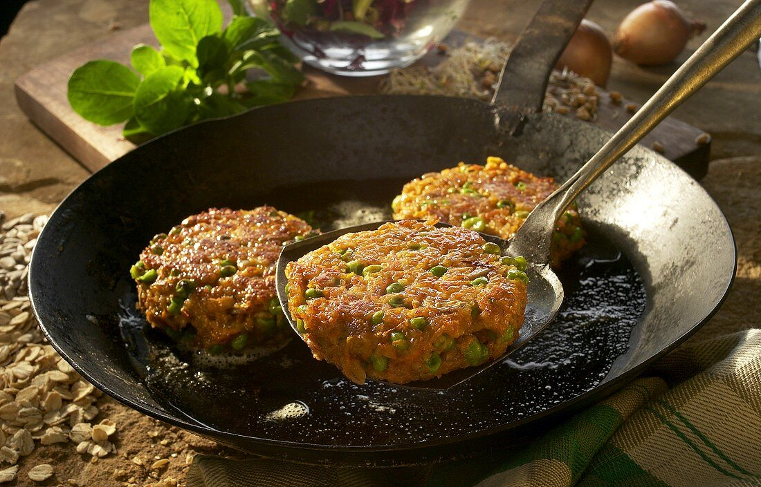Green rye and vegetables cakes in the pan