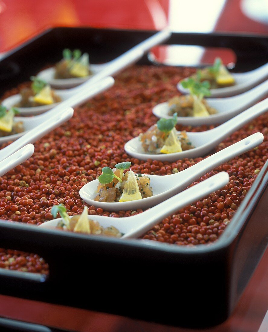 Tuna carpaccio on soup spoons as party snacks