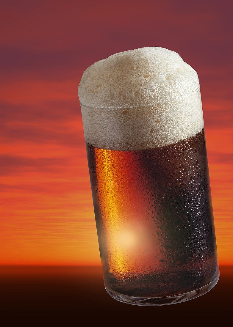 Glass of Altbier in front of  sunset (collage)
