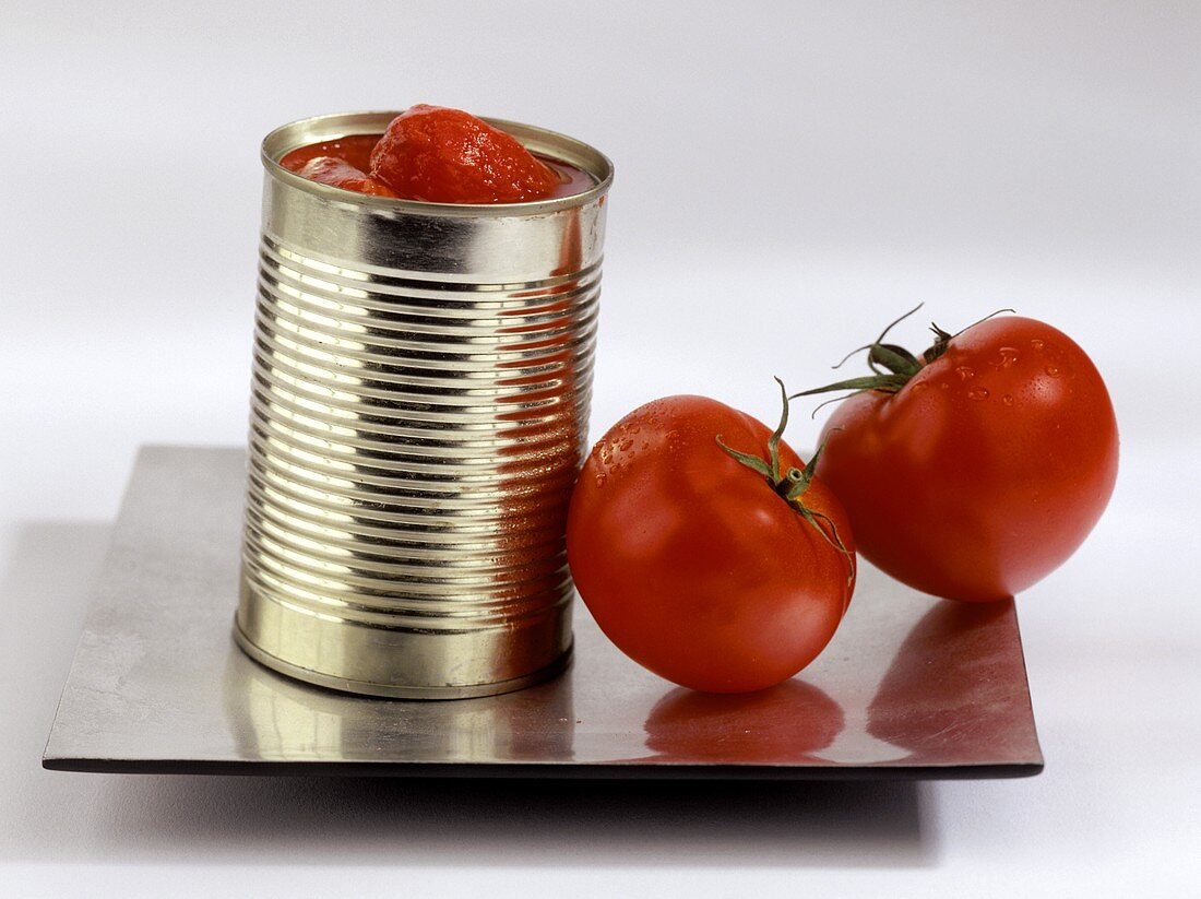 Peeled tomatoes in a tin with two tomatoes