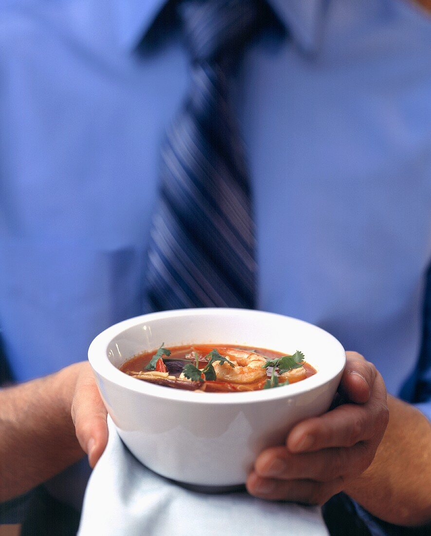 Man holding small bowl of tomato & orange soup with shrimps