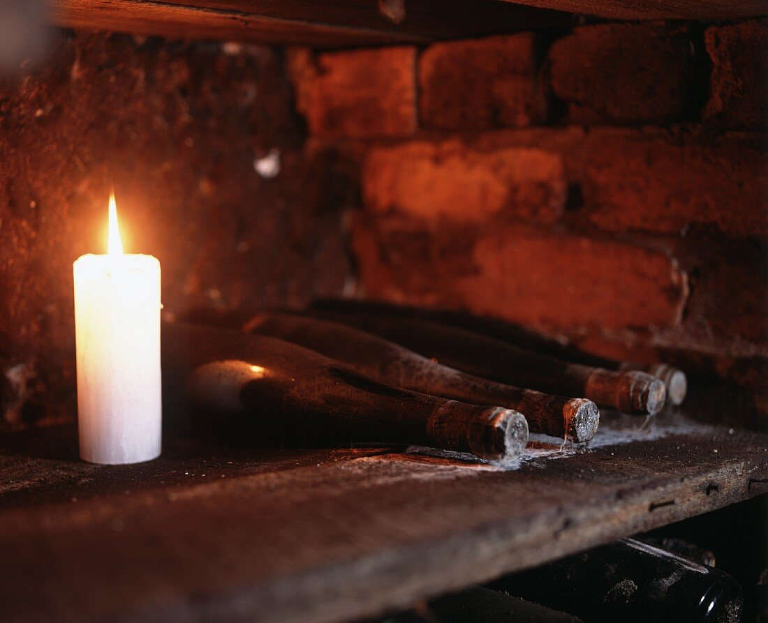Candles beside wine bottles in Seppelt wine cellar, Victoria