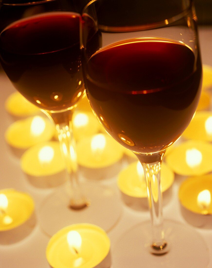 Two glasses of port wine surrounded by burning candles