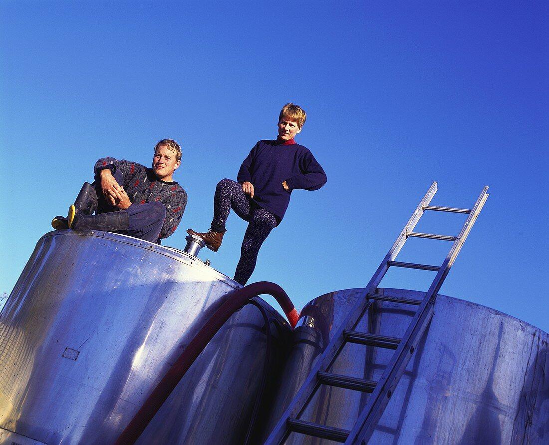 Oliver Masters and Phyll Patti on wine tank, Ata Rangi, Waipar