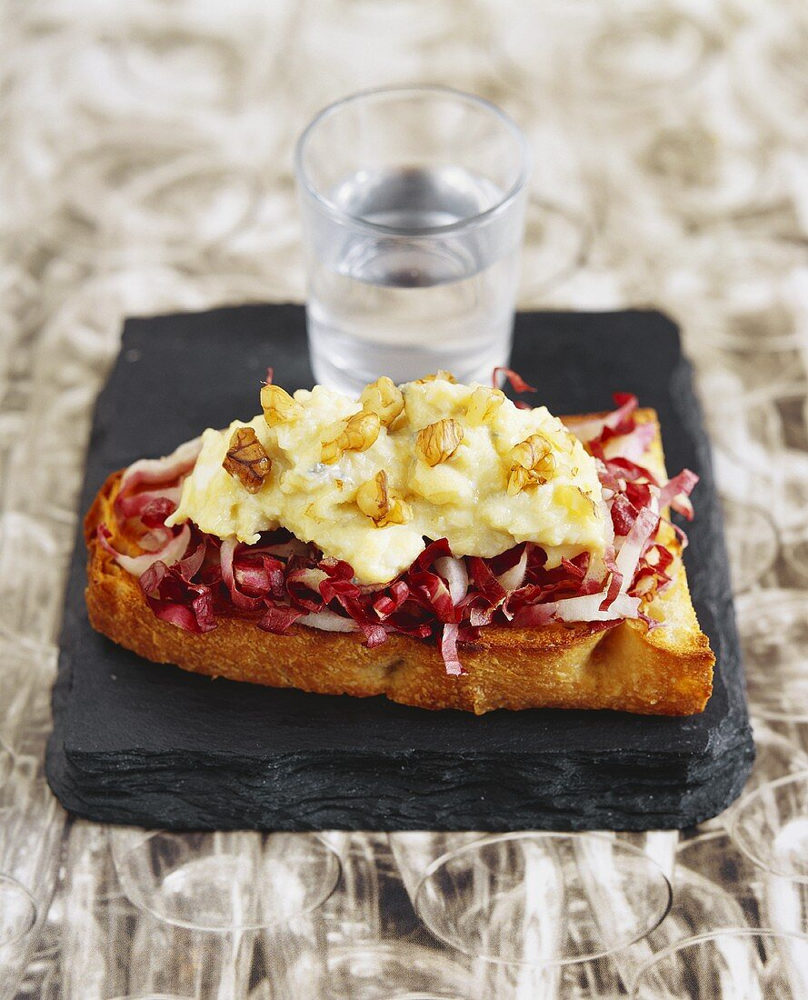Radicchio and blue cheese on toast and a glass of water