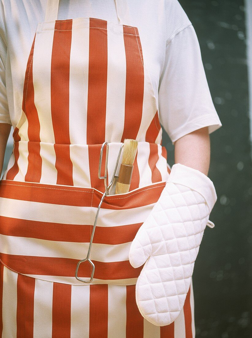 Person in barbecue apron with barbecue utensils (close-up)
