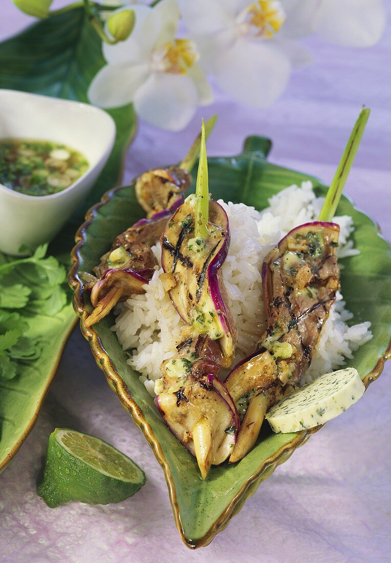 Barbecued duck breast kebabs with herb butter on rice