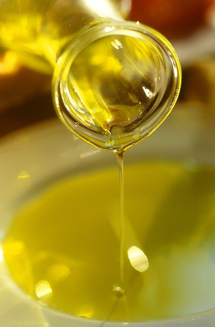 Pouring a thin stream of olive oil on to a plate