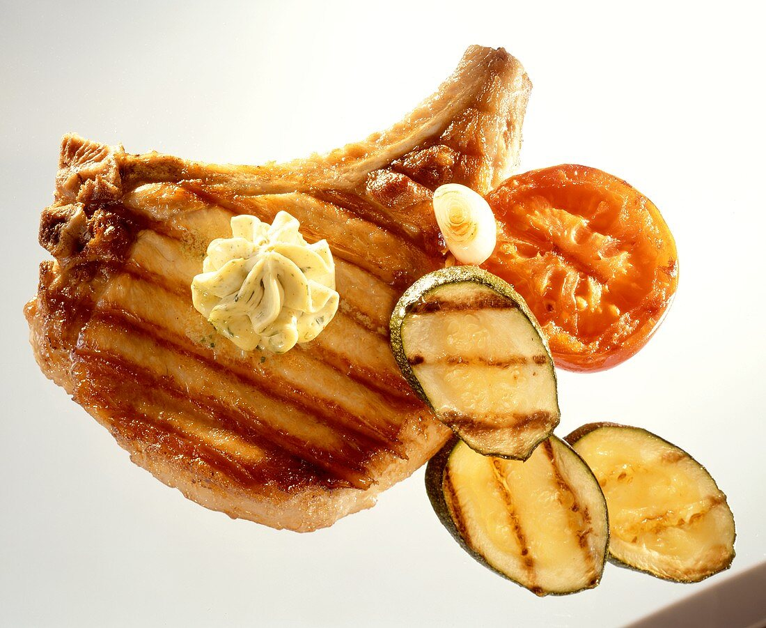 Barbecued pork cutlet with herb butter & barbecued vegetables