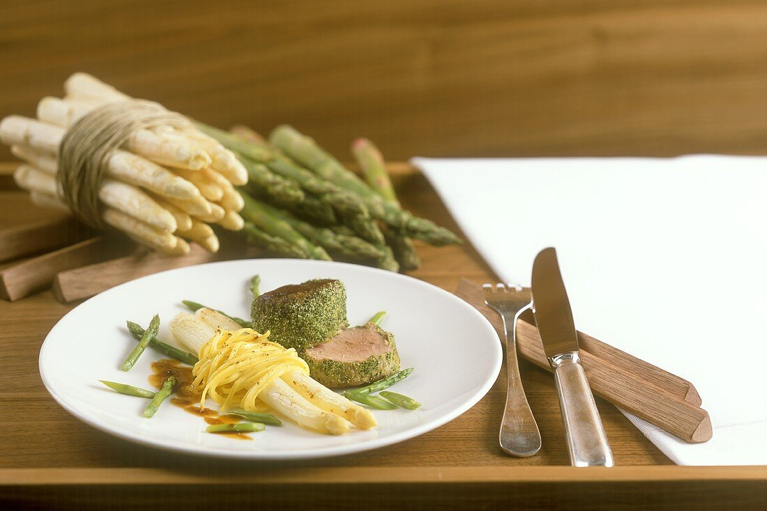 Veal fillet in herb coating with noodles and asparagus