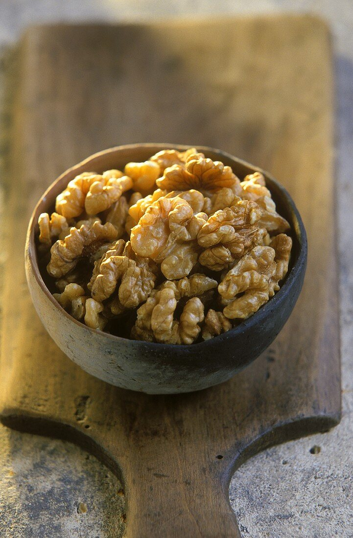 Terracotta bowl of walnut kernels on a wooden board