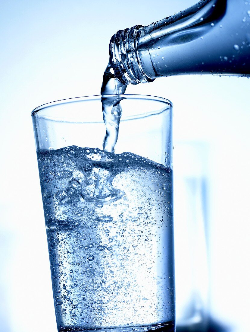 Pouring mineral water out of bottle into glass