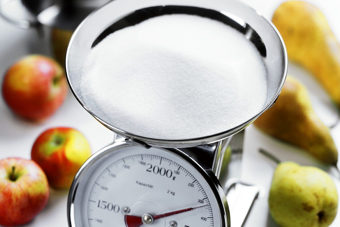 Sugar on kitchen scales; fruit