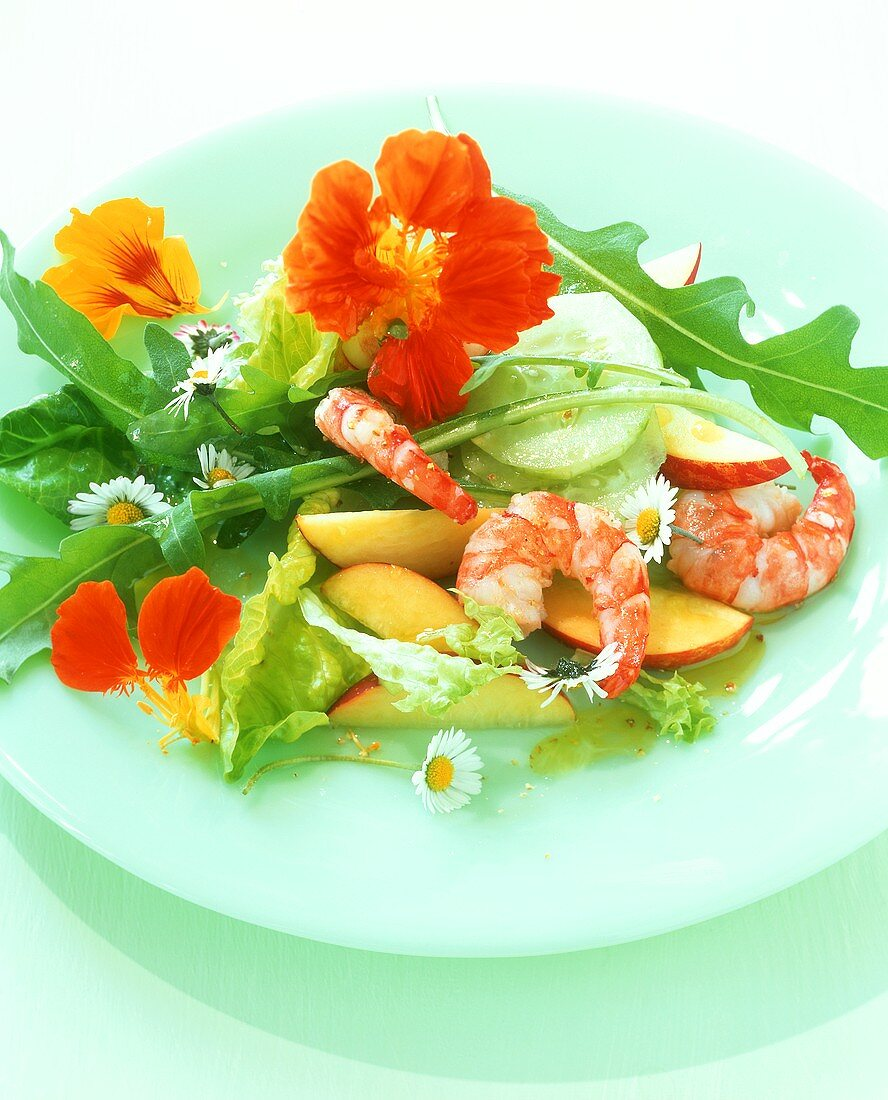 Colourful salad with apples, shrimps and edible flowers