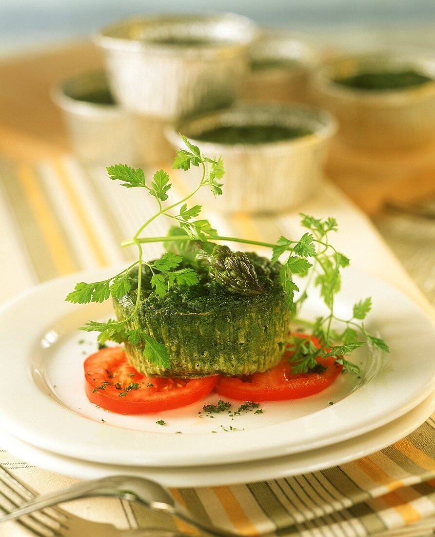 Savoury spinach muffins with green asparagus on tomato slices