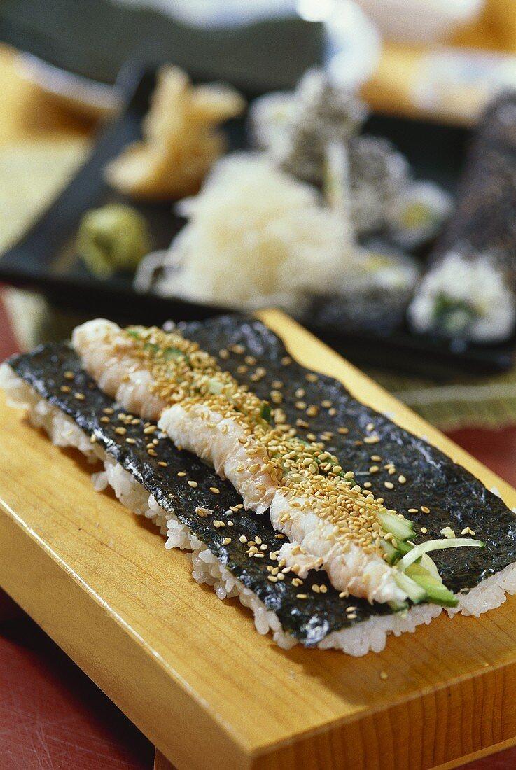 Preparing California maki (inside-out sushi)