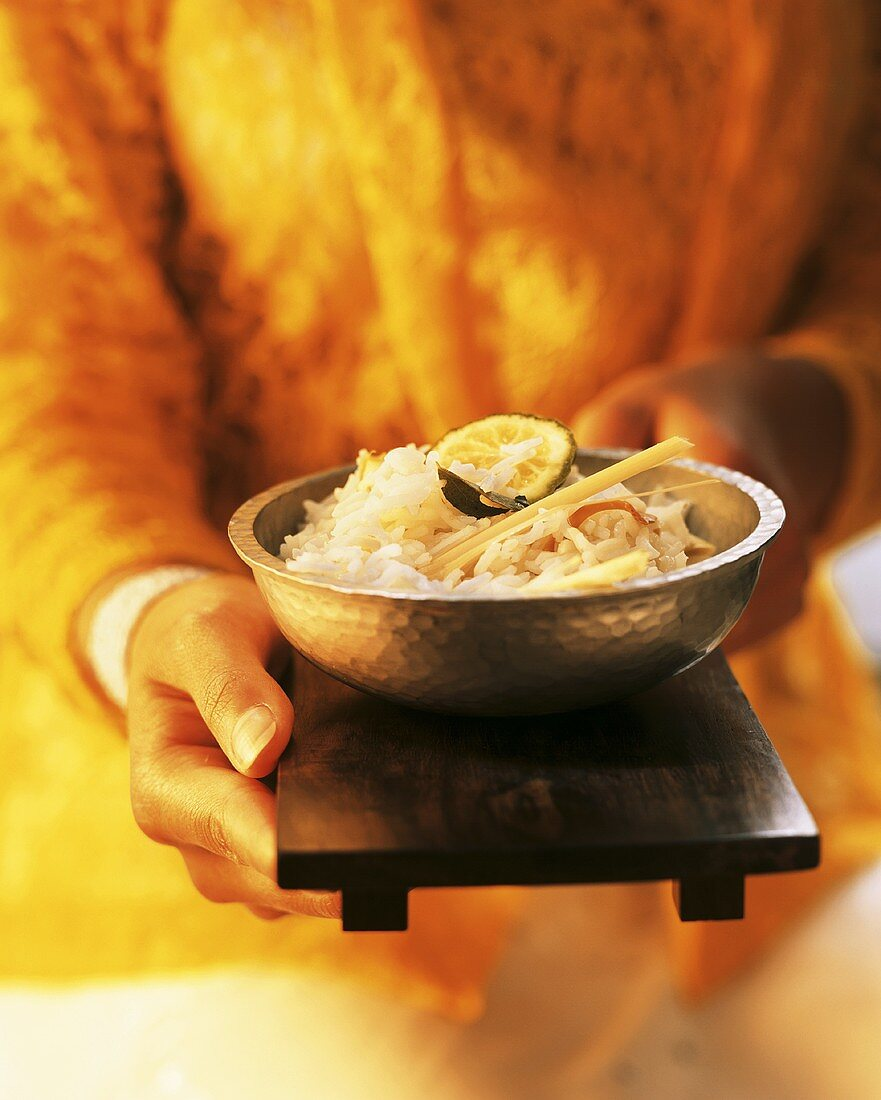 Hand holding wooden tray with rice bowl
