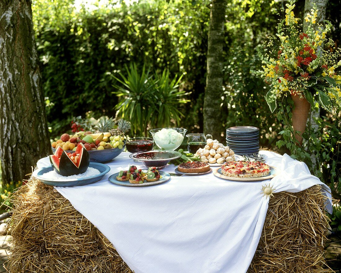 Dessert and cake buffet on bales of hay for a summer party