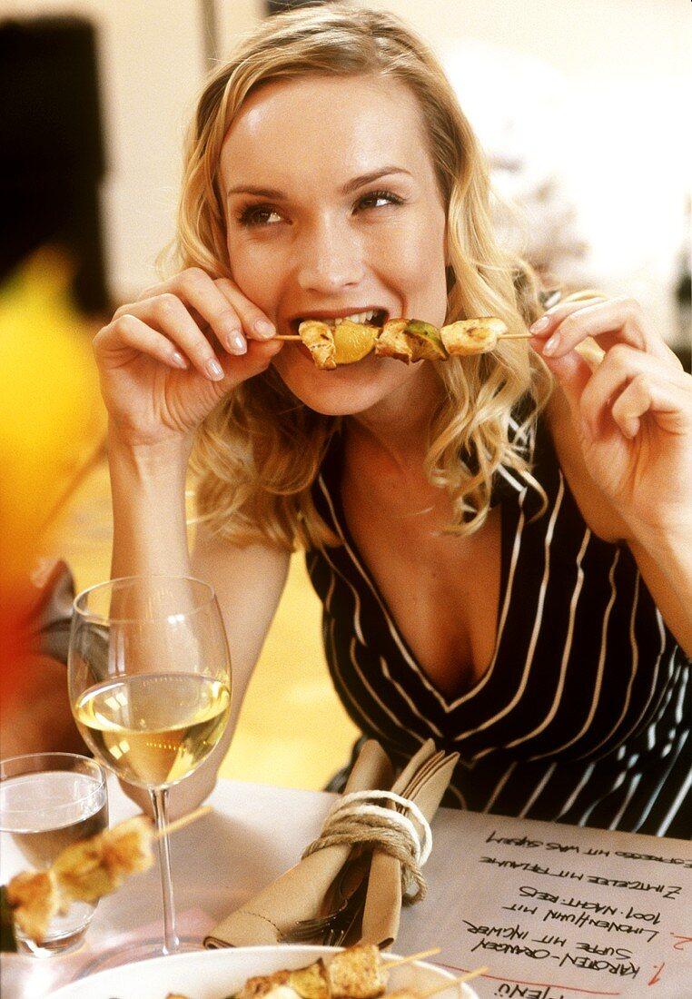 Young woman at romantic meal nibbling chicken kebab