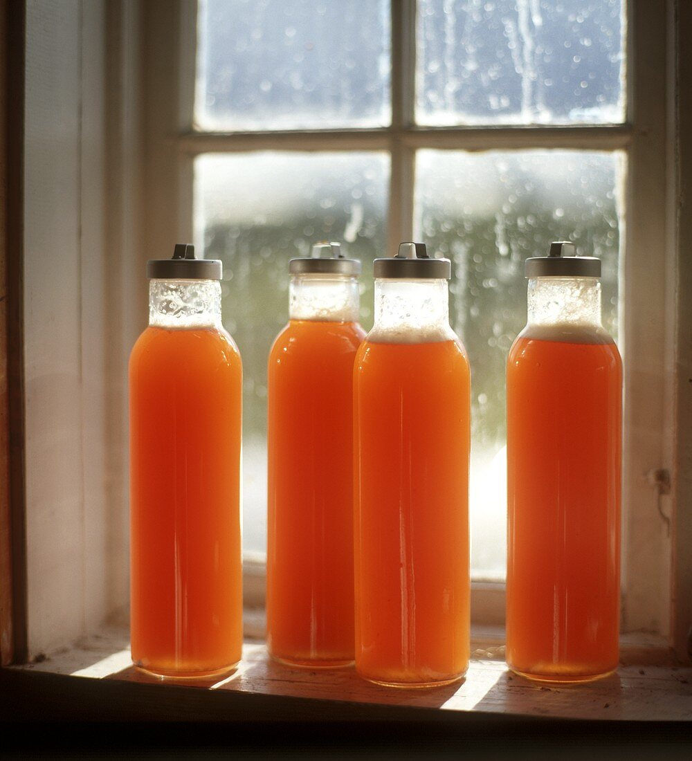 Freshly pressed apple and carrot juice in bottles