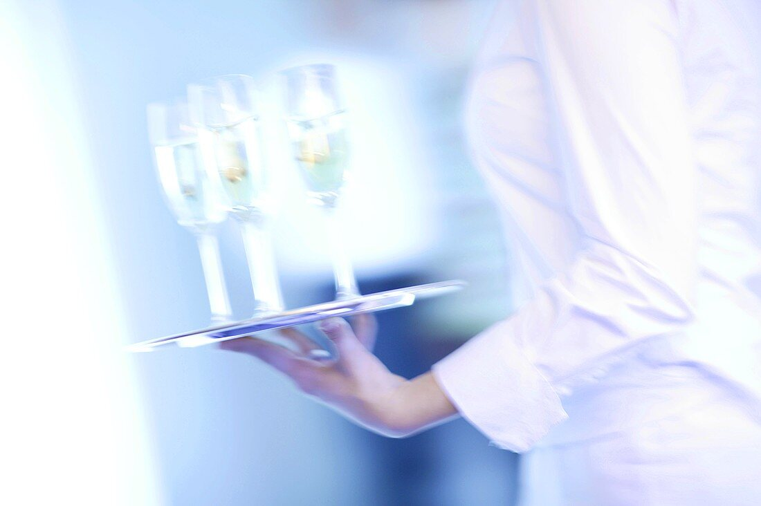 Waitress carrying tray of champagne glasses