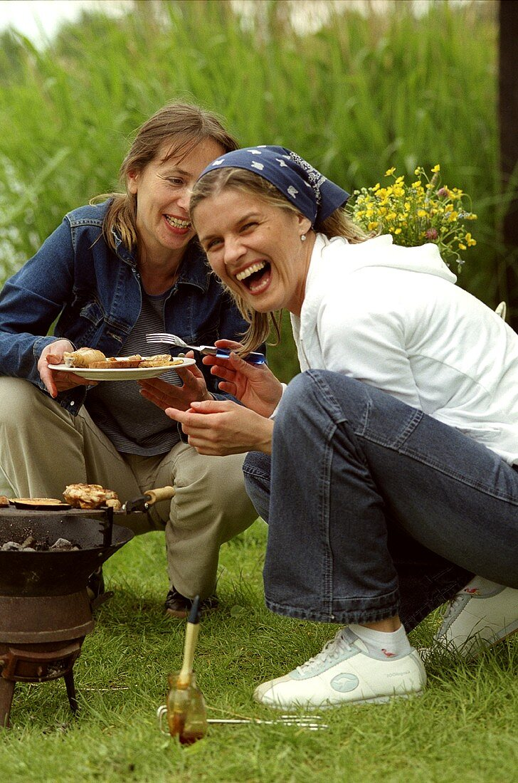 Two young women barbecuing out of doors
