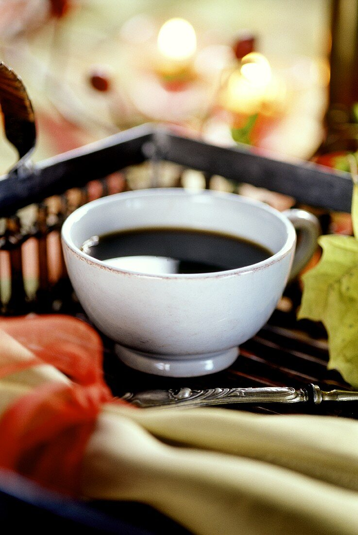 Cup of black coffee on tray with autumn decoration