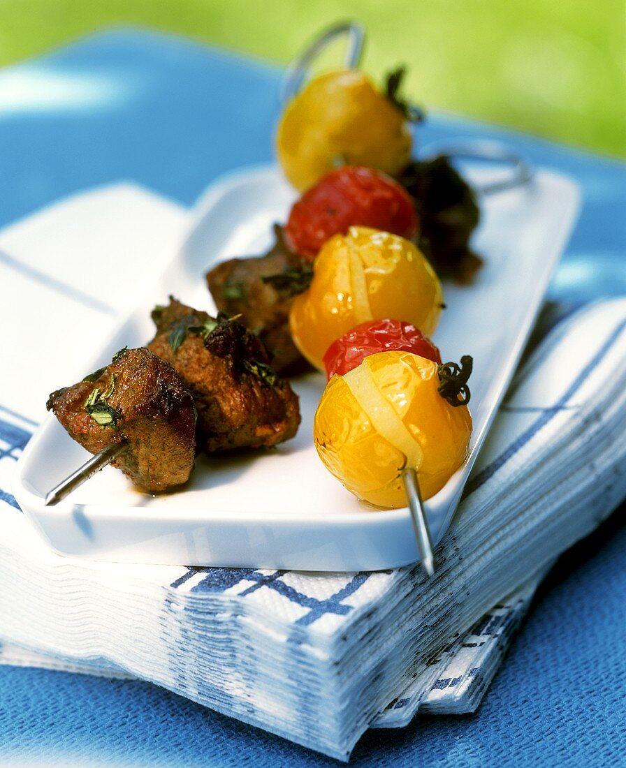 Barbecued meat kebab with herbs & skewered cocktail tomatoes