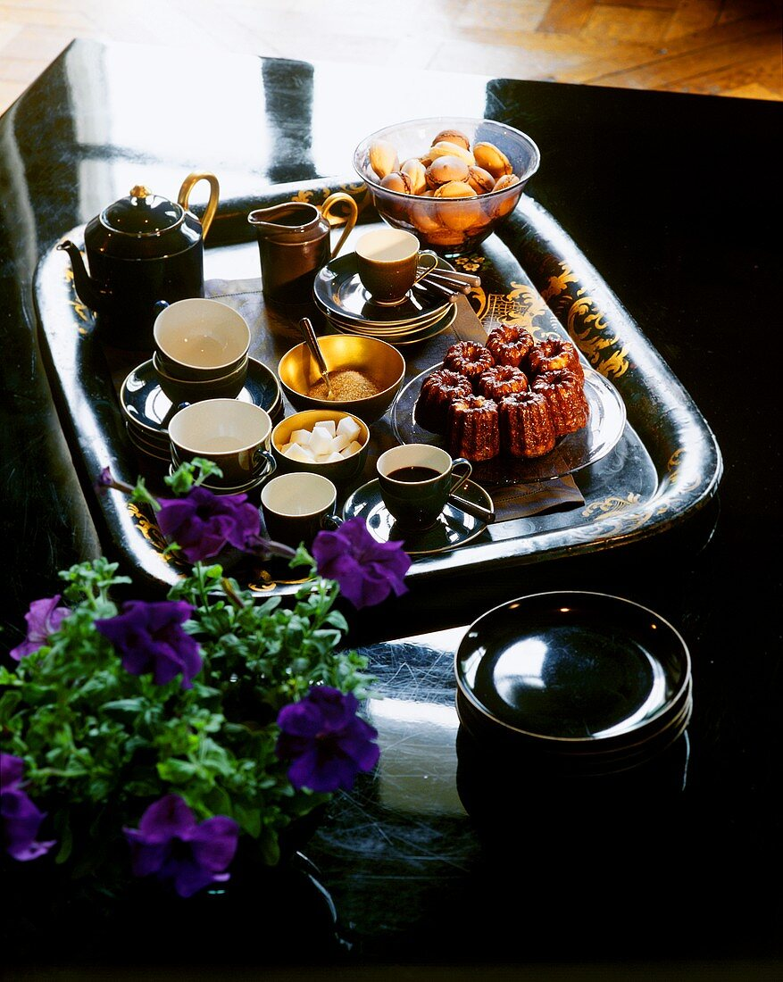 Tray with coffee, tea, French canneles and macaroons